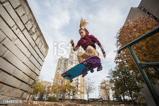 Skater woman jumping on her skate. She is jumping in the air and performing a difficult jump.
