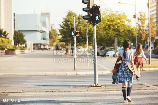 Skater girls are crossing the pedestrian crosswalk. Copy space.