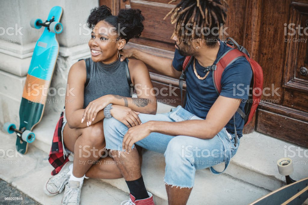 Skating couple siting on stairs royalty-free stock photo