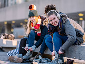 Young Caucasian teenage women putting on skates at the skating rink in downtown area of big city in North America. Both are dressed in heavy winter clothes. In the background, unrecognizable people skating or getting ready to go on ice. Both of them is looking at camera.