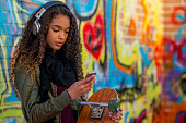 A teenage girl is listening to music from her smartphone and is holding her skateboard. There is a brightly painted graffiti wall in the background.