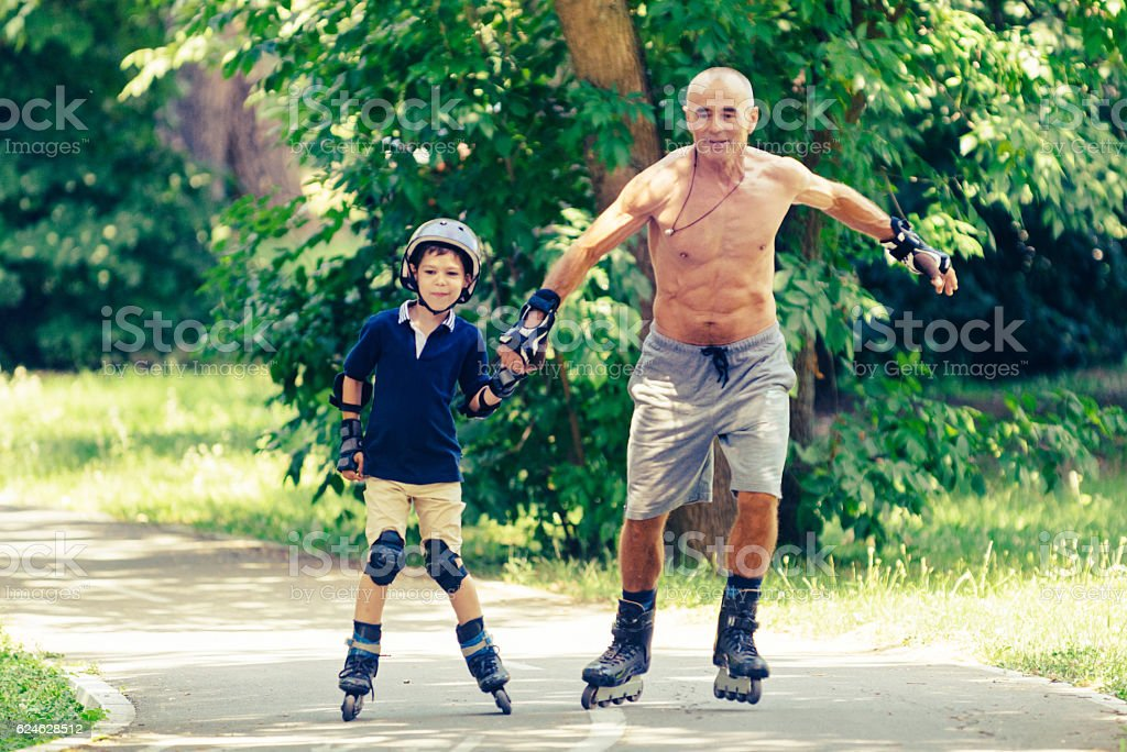 Skating with grandpa in the park stock photo