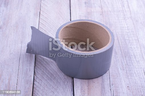 istock A skein of gray tape on an old wooden table. 1190894138