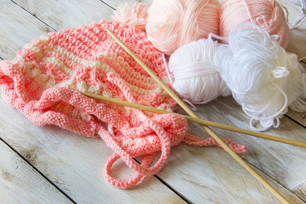 Skeins of wool with wood knitting needles and baby hat – Foto