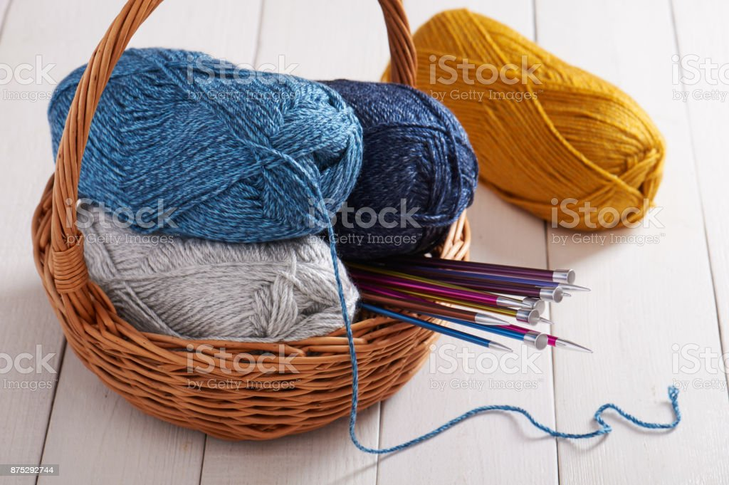 Skeins of yarn and knitting needles in basket stock photo