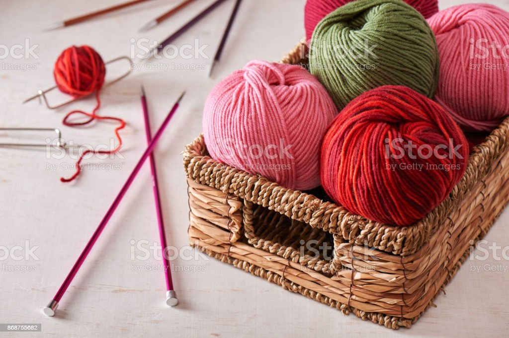 Skeins of yarn in basket and knitting needles stock photo