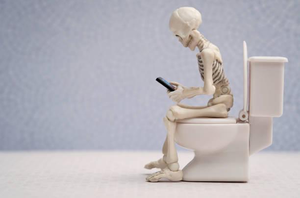 skelet en zijn smartphone - cell phone toilet stockfoto's en -beelden