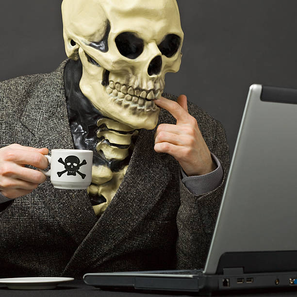 skeleton drinks poisonous coffee at table with laptop - coffe with death bildbanksfoton och bilder