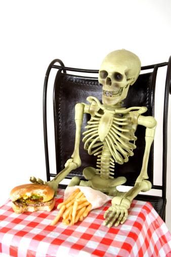 Skeleton eating burger and fries