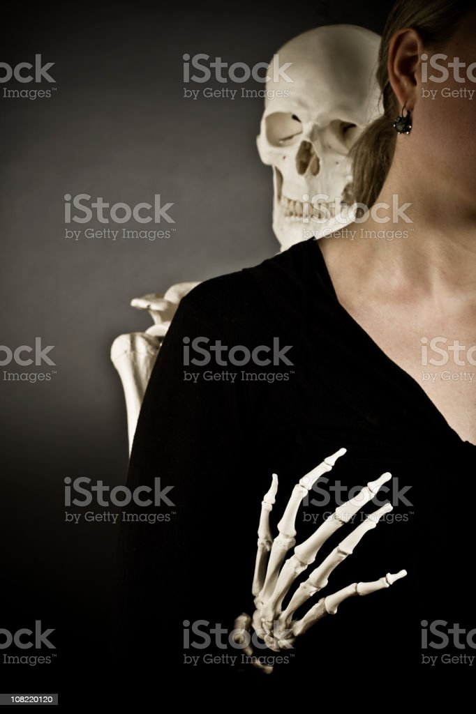 Skeleton Grabbing Woman's Chest Suggestively From Behind stock photo