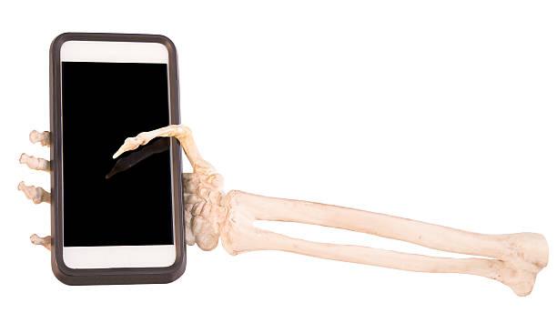 skelett hand holding handy - skelett hand stock-fotos und bilder