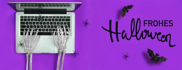 skeletthände tippen in laptop und halloween-text in deutsch - handschriftliche typografie stock-fotos und bilder