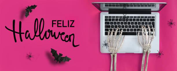 skelett hände tippen in laptop und halloween-text in spanisch - handschriftliche typografie stock-fotos und bilder