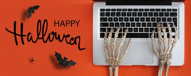 skeletthände tippen in laptop - handschriftliche typografie stock-fotos und bilder