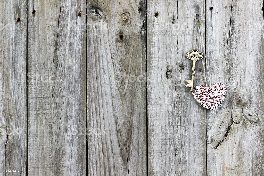 Skeleton key and heart hanging on door stock photo