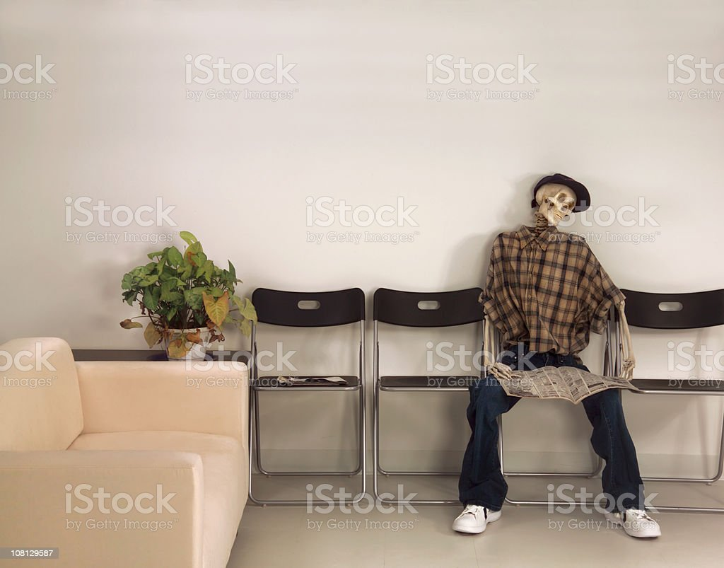 Skeleton Man Sitting Waiting Room with Newspaper royalty-free stock photo