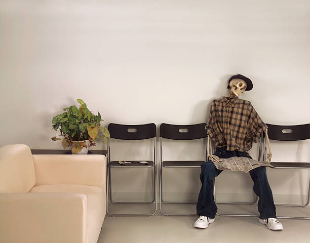Skeleton Man Sitting Waiting Room with Newspaper stock photo