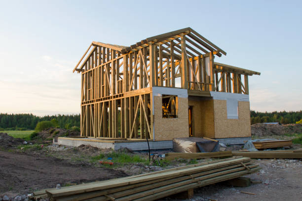 Skeleton of a wooden two-story cottage surrounded by building materials Skeleton of a wooden two-story cottage, partially wired with OSB panels, surrounded by building materials and garbage. Unfinished country house in rays of setting sun in the background of the forest building activity stock pictures, royalty-free photos & images