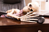 Skeleton of man who died while waiting 'on hold'.  Telephone.