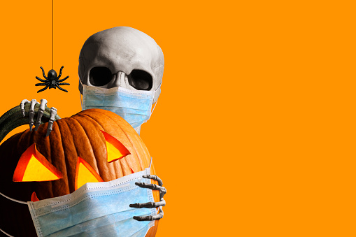 A skeleton wraps its hands around and peeks out from behind an illuminated jack o'lantern as a spider hangs from its web isolated against an orange background.  Both the skeleton and the jack o'lantern wear a protective face mask in the time of Covid-19.