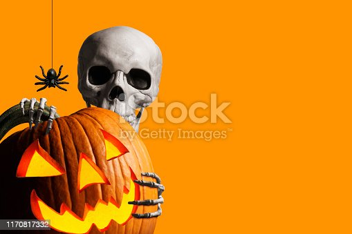 A skeleton wraps its hands around and peeks out from behind an illuminated jack o'lantern as a spider hangs from its web isolated against an orange background.