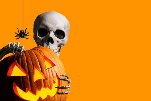 scheletro sbircia da dietro un jack o'lantern di fronte allo sfondo arancione - halloween foto e immagini stock