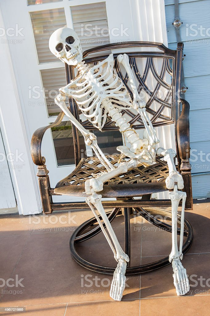 skeleton sit at the armchair and wait stock photo