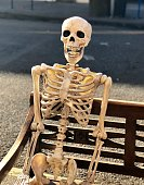Funny Halloween decoration - skeleton sitting on a bench on a city street