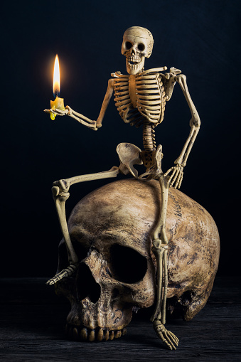skeleton sitting on big skull with burning candle in hand