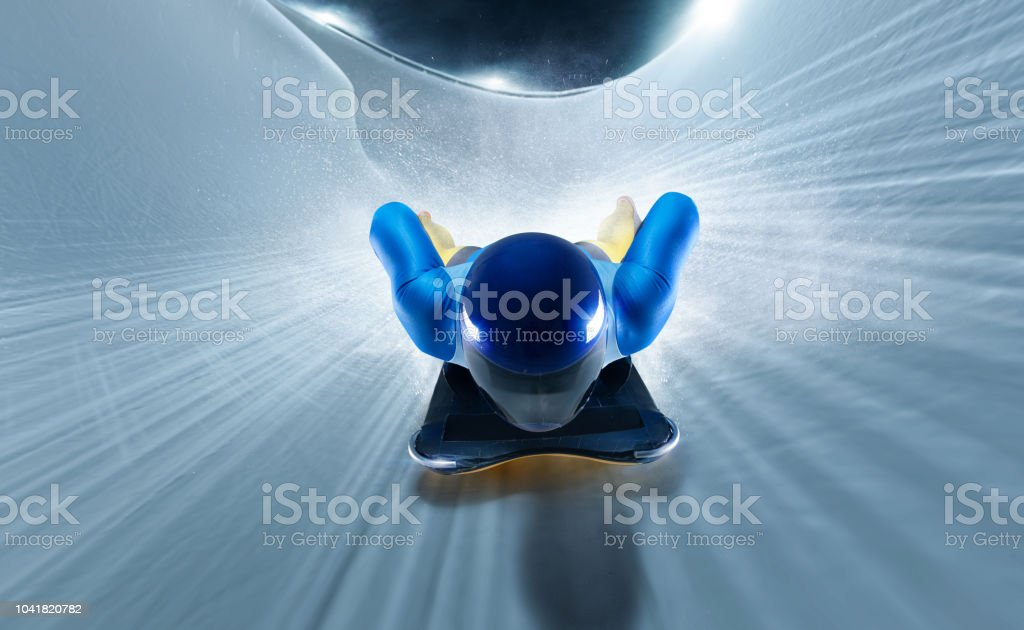 Skeleton sport. Bobsled. Luge. The athlete descends on a sleigh on an ice track. Olympic winter sports. stock photo