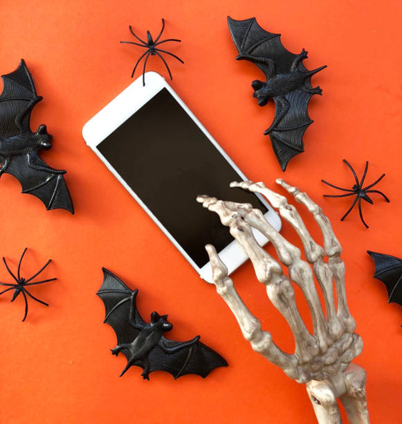 skelett mit telefon - skelett hand stock-fotos und bilder