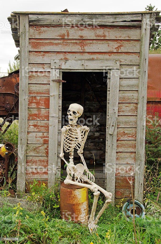 Skeleton Waiting Outside Outhouse stock photo
