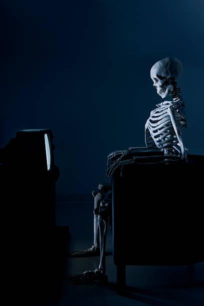 scheletro guardare la televisione in the dark - divano procrastinazione foto e immagini stock