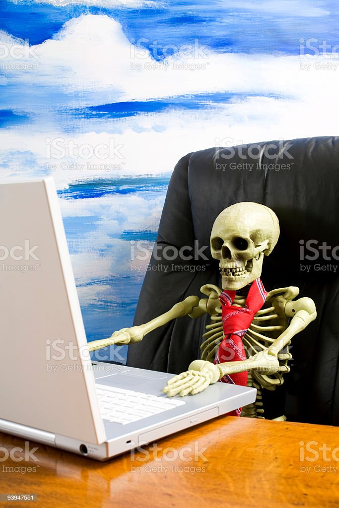 Skeleton wearing tie in executive chair with laptop on desk stock photo