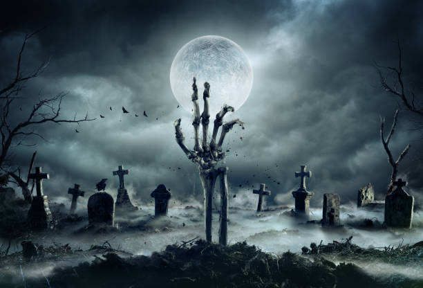 skeleton zombie hand rising out of a graveyard - halloween - cimitero foto e immagini stock