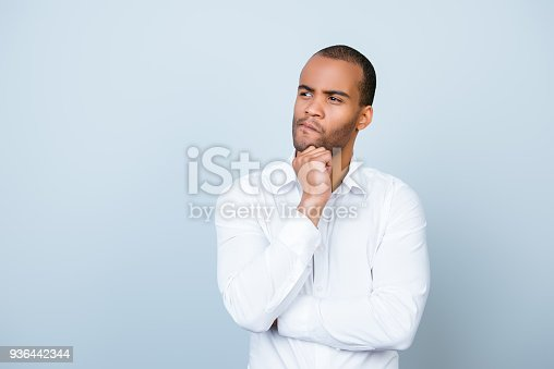 istock Skeptic, unsure, uncertain, doubts concept. Young african guy in formal wear is looking sceptical, has a grimace of distrust on light blue background 936442344