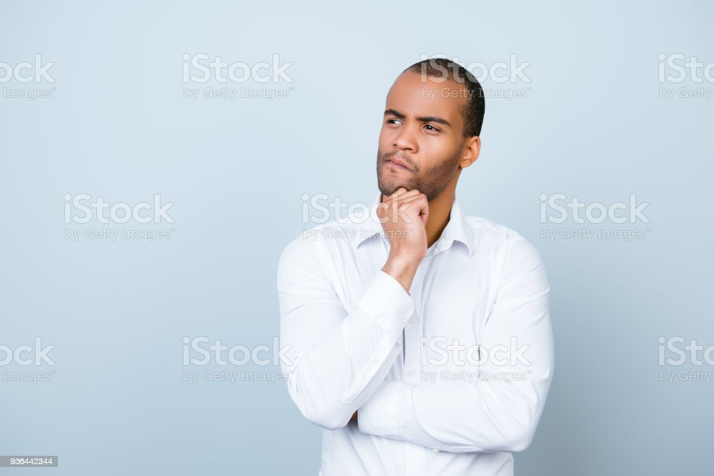 Skeptic, unsure, uncertain, doubts concept. Young african guy in formal wear is looking sceptical, has a grimace of distrust on light blue background stock photo