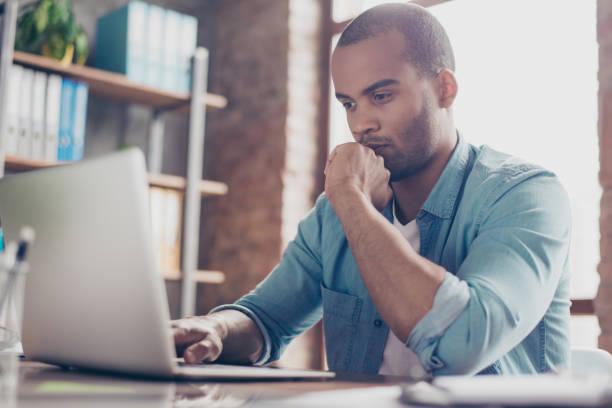 scepticus jonge afro freelancer is overgaat zittend op het kantoor in casual smart, analyseren van de gegevens in de computer - achterdocht stockfoto's en -beelden