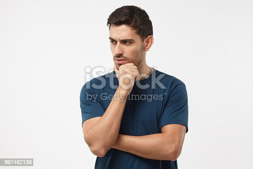 Skeptical and dissatisfied young man in blue t-shirt touch his chin with hand. Doubt concept
