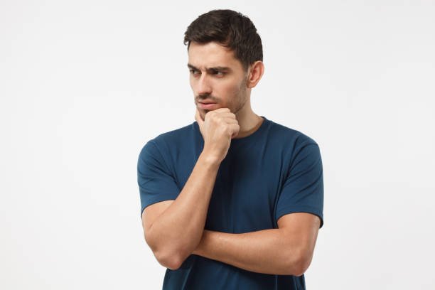 skeptical and dissatisfied young man in blue t-shirt touch his chin with hand. doubt concept - cynic stock pictures, royalty-free photos & images