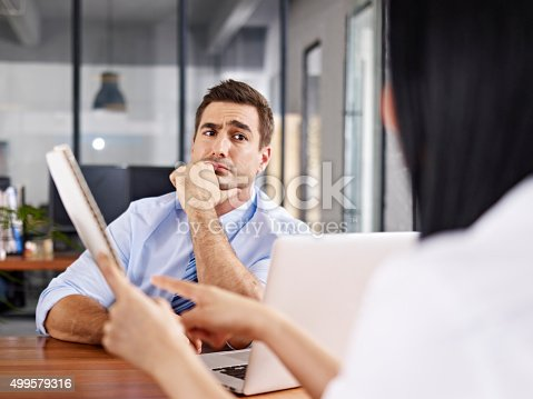 istock skeptical interviewer looking at interviewee 499579316