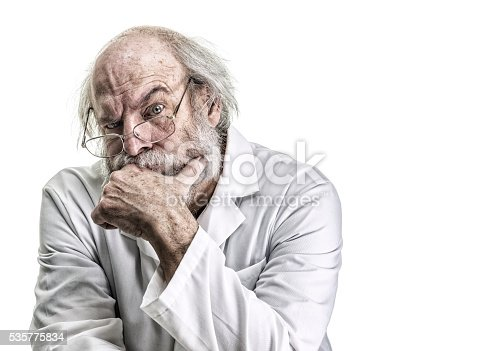 A bizarre, skeptical, messy, brilliant, genius, tangled haired psychiatrist (or he might be a poorly groomed doctor, scientist, pharmacist, or some other medical occupation professional) is looking at the camera while listening closely with a serious, raised eyebrow facial expression. He is a balding senior adult man with a gray beard and mustache. He is wearing a white lab coat and is sitting with left hand covering his chin. Canon 5D Mark III.