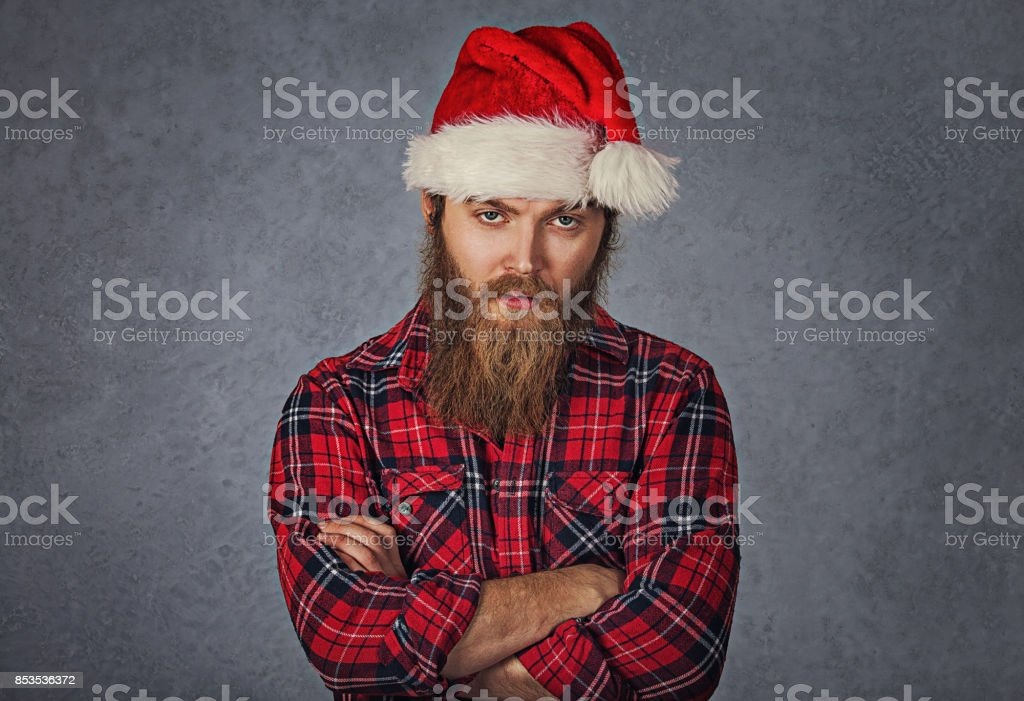 Skeptical tired bearded man in santa claus hat isolated grey gray background. stock photo