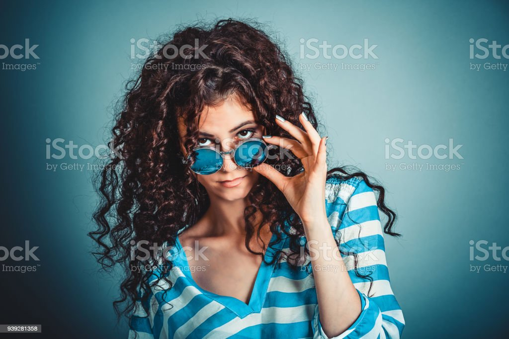 Skeptical woman holding sunglasses down skeptically stock photo