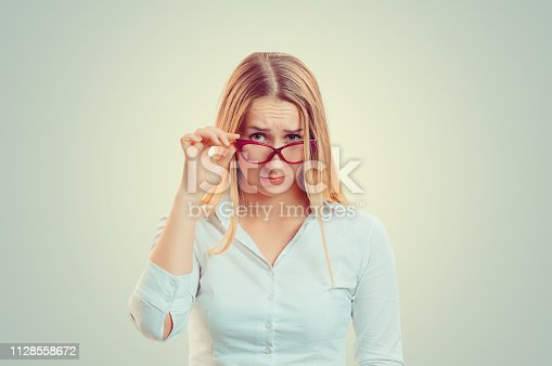 Head shot serious doubtful woman wife holding sunglasses down skeptically looking at you isolated green yellow wall background, white shirt. Human face expression body language, attitude perception