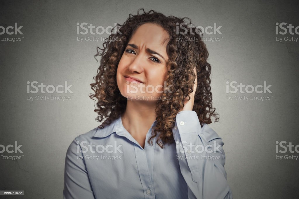 skeptical young curly brown hair woman stock photo