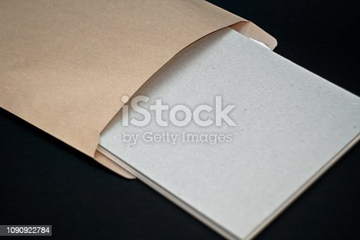 istock Sketchbook with a hard cardboard cover and spring pad in a craft envelope on black background. Close-up. 1090922784
