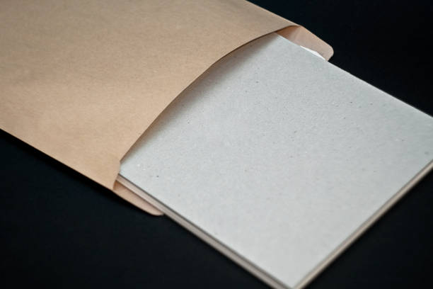 Sketchbook with a hard cardboard cover and spring pad in a craft envelope on black background. Close-up. stock photo