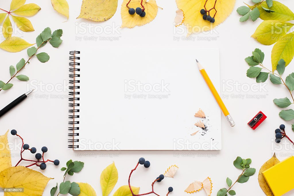 Sketchbook with pencil in autumn leaves frame stock photo