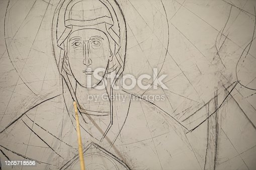 istock Sketching the figure of the Virgin Mary on the wall of the church 1265718556
